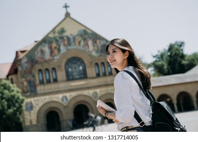 asian college girl carrying backpack and school book walking to church praying in the morning before go to class in university. smart woman study as exchange student program short term.