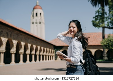 asian college girl standing outdoor going to class at school in summer tour program. elegant smart exchange student study overseas in stanford usa. young woman freshman in new semester cheerful smile