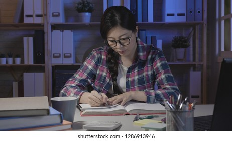 asian college girl studying the night before final exam. young smart female student reading book and writing notes with pencil sitting at desk in dark room at home in midnight. woman in glasses focus