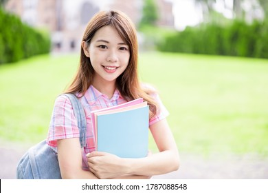 Asian college student smile to you with books holding in hands on campus