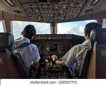 Asian commercial pilots in cockpit operating the airplane to avoid cloudy weather. Seen from inside cockpit from back seat. Captain is observing the path to go while copilot controlling the aircraft.
