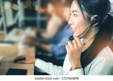 Asian confidence operator woman agent with headsets working in a call center at night Environment with her colleague team as customer service.they are smiling while working in office at night.