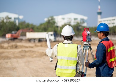 Asian Construction engineer holding drawing and smart tablet with foreman worker checking construction site for new Infrastructure construction project.photo concept for engineering work