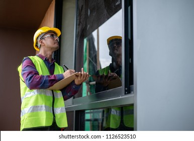 Asian construction worker or building inspector checking outdoor building construction structure or decoration detail by using check list.