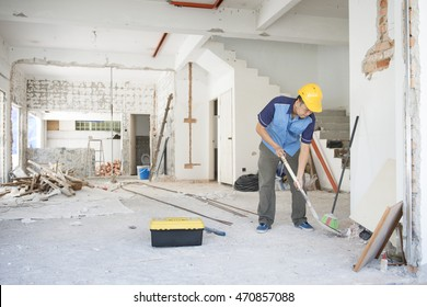 Asian construction worker with hardhat working at site, house renovation.