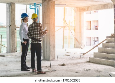 Asian contractor and engineer inspecting material in construction building.