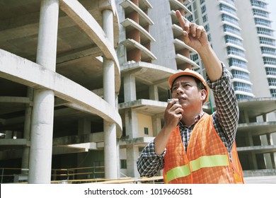 Asian contractor using walkie-talkie to explain employees what to do