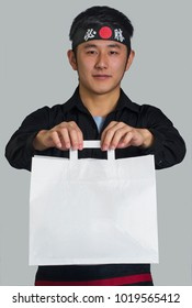 Asian cook hold a sushi roll dish take away bag and wearing a black bandana with Chinese word ( victory )