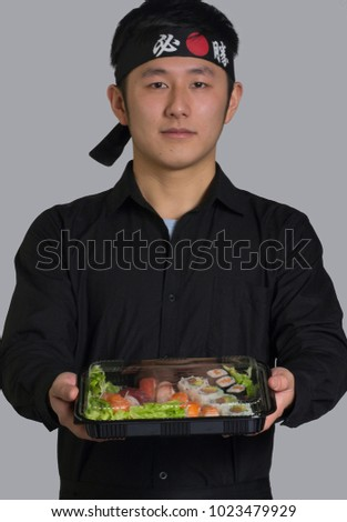 Asian cook holding take away sushi set on plastic container and wearing a  black bandana in 920563a138f