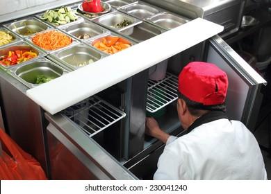 Un cuisinier asiatique dans une cuisine travaillant sur un buffet de légumes
