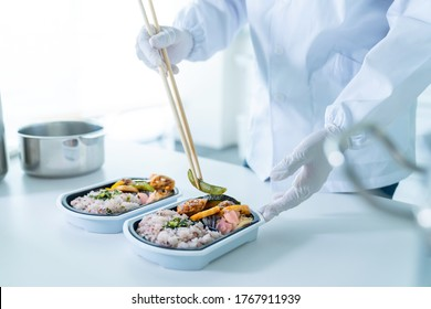Asian cook making a bento in the kitchen. Restaurant. Lunch vendor.
