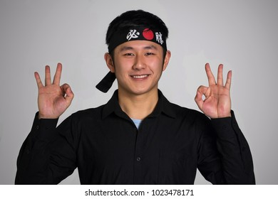 Asian cook making positive hand sign and wearing a black bandana in Chinese word translation ( Victory )
