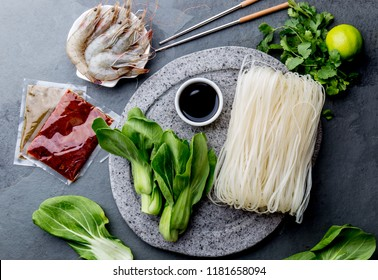 Asian cooking ingredients: rice noodles, pok choy, sauces, raw shrimps. Asian food concept Chinese or Thai cuisine