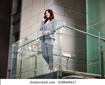 asian corporate executive business woman standing on top of stairs making a call using mobile phone in modern office building, low angle view.