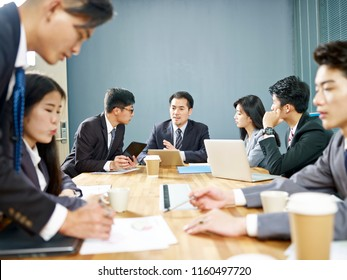 asian corporate people discussing business in groups.