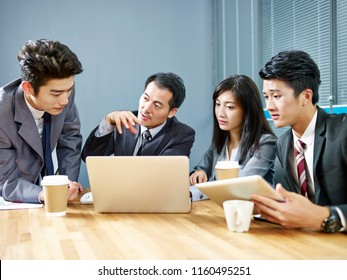 asian corporate people meeting in office discussing business using laptop computer.