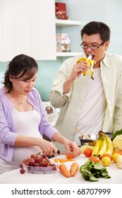 Asian couple activity in kitchen, with lots of fruit and vegeteable, where the couple eating fruit