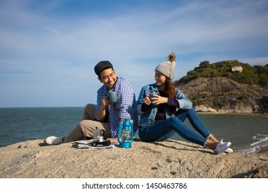 Asian couple in blue shirt  with coffee cup and vintage camera picnic on the mountain near the beach sea view happy and smile face