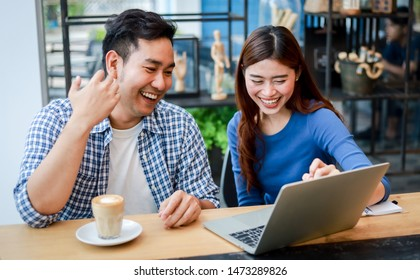 Asian couple in blue shirt drinking coffee talking and working with computer laptop smile and  happy mood in coffee shop cafe