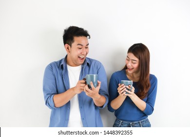 Asian couple in blue shirt on white background with cup of coffee happy and smile mood