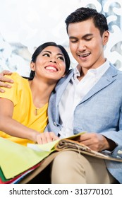 Asian couple buying sofa in furniture store, sitting on couch choosing color and material