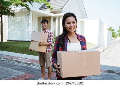asian couple with cardboard box standing in front of their house