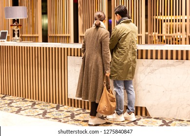 Asian couple checking in the hotel at hotel reception.