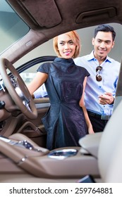 Asian couple choosing luxury car in auto dealership looking at the interior