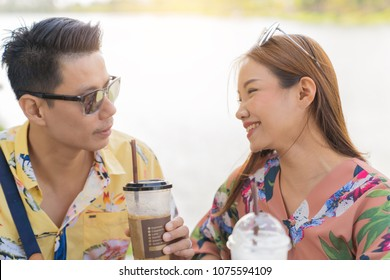 Asian couple drinking coffee and smileing on river background, sunny light effect, vacation holidays happiness couple concept.