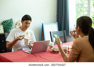 Asian couple eating instant noodles and pizza together in the kitchen. Enjoy for meal healthy. Lifestyle for dinner and stay at home. woman eating instant noodles.