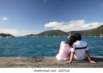Asian couple enjoying the beautiful sea landscape while sitting on a piece of wood