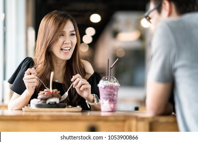 Asian couple enjoying date and talking in cafe. Happy smile woman chatting and laughing with boyfriend at restaurant cafe.