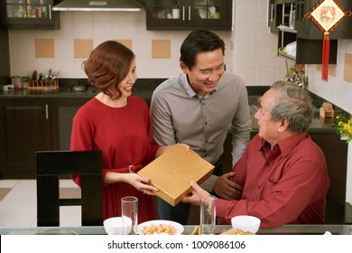 Asian couple giving present for Tet to grandfather