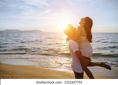 Asian couple are happy with love on the beach at summer weekend holiday Valentines' day.