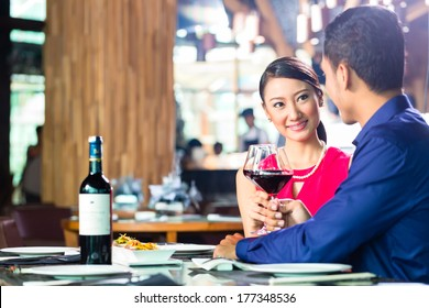 Asian couple having dinner and drinking red wine in very fancy restaurant with open kitchen in background