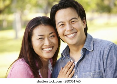 Asian couple head and shoulders portrait outdoors