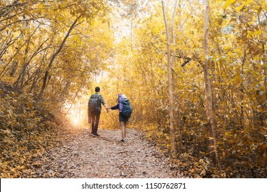 Asian couple hipster hiking on mountain holiday wild adventure  in autumn forest park . Helping ,helps ,business sucess and team work concept.