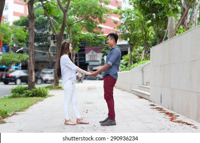 Asian couple hold hands happy smile looking to face dating walking on city street