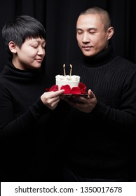 Asian couple holding cakes in studio