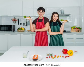 Asian couple holding dish salmon steak a healthy breakfast with happiness in the kitchen at their home. Lifestyle and healthy concept.