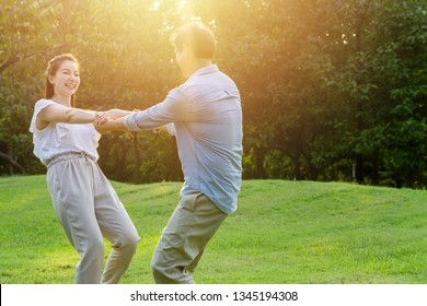 Asian couple holding hands and spinning around while standing together outdoor.