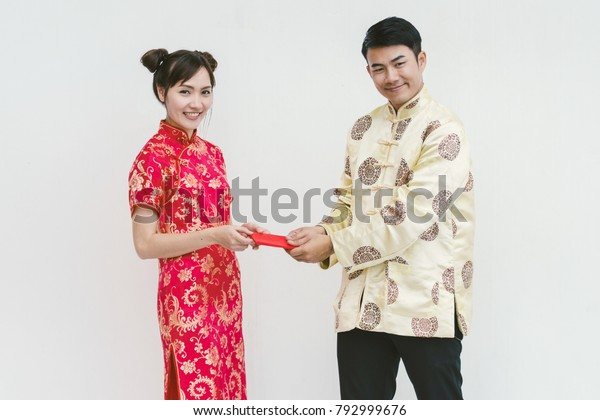 Asian couple holding red Chinese new years envelopes. Chinese new year.