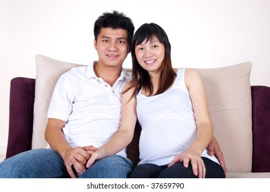 Asian couple. Husband and 8 months pregnant wife sitting on sofa.