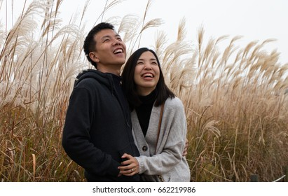 an asian couple is looking in the sky with happiness