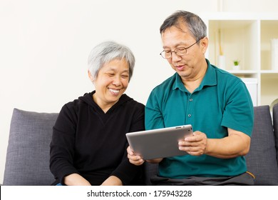 Asian couple looking at tablet together