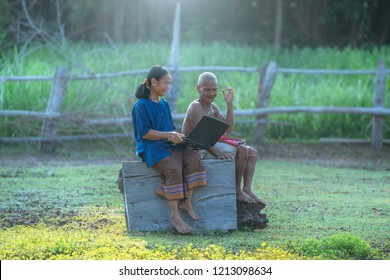 Asian couple love looking a laptop outside,countryside,Thailand,