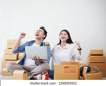 Asian Couple lover checking order and prepare parcel for customers at home,seller online concept.
