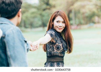 Asian couple lovers hold one's hands under a vast field of nature in a park.