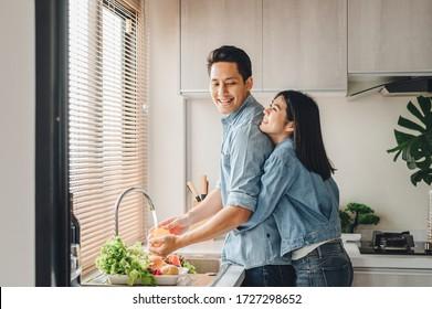 Asiatische Paare umarmen in der Küche beim Kochen zu Hause. Eine Frau umarmt einen Mann, der Gemüse von hinten wäscht.