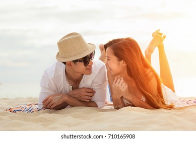Asian couple lying Honeymoon at sunset tropical beach in Thailand